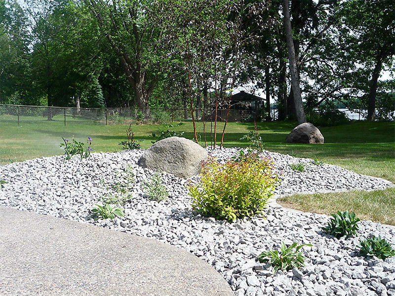 Landscape rock with trees, shrubs, and hostas