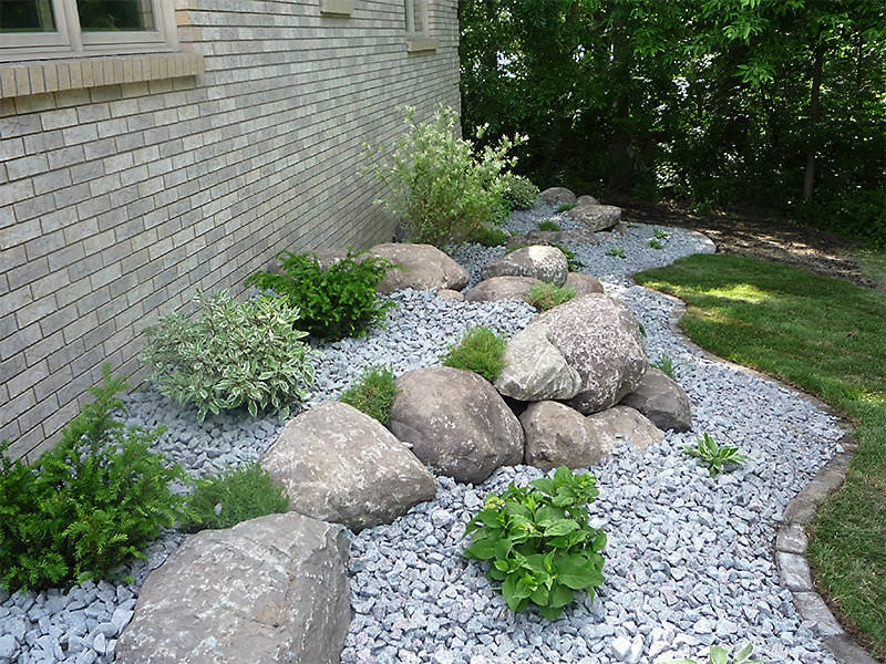 Landscaping around house with boulders, rocks, and shrubs