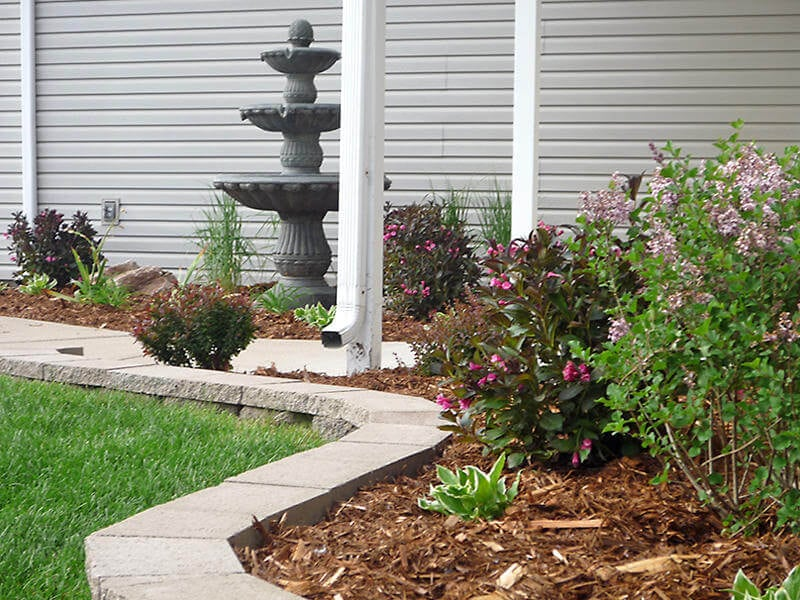 Paver stone border around mulch flowerbed with shrubs