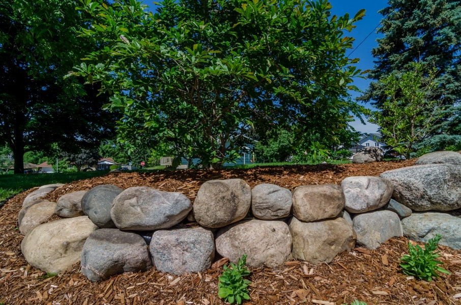 Landscape boulders used as retaining wall in mulch garden