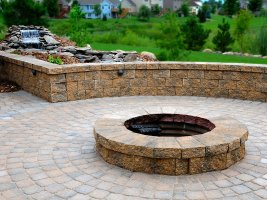 Outdoor living space with waterfall, patio, and fire pit
