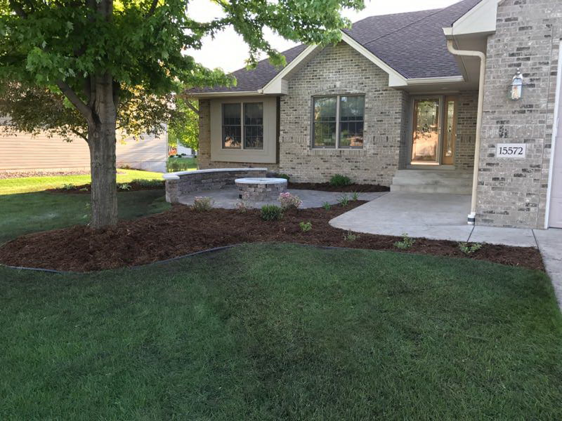 Patio with firepit and mulch around tree in front yard