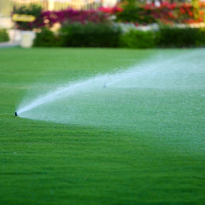 Lawn sprinkler spraying fertilizer in yard
